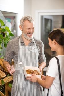 Fresh buns. joyful friendly bearded man in apron showing bread buns in open box to customer in store