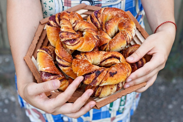 Fresh buns with berries. hands in the frame.
