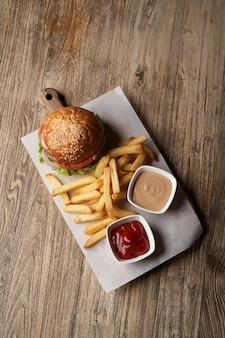 나무 절단 보드에 신선한 햄버거와 감자 튀김. 패스트 푸드, 정크 푸드