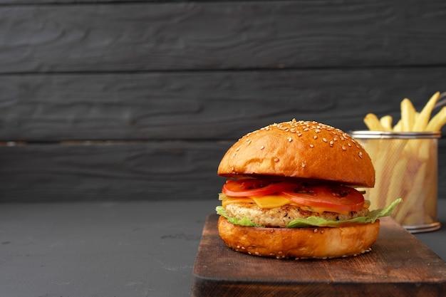 新鮮なハンバーガーと黒い木製の背景、正面図のフライドポテト