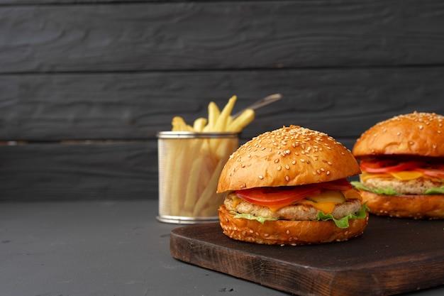 黒い木製の新鮮なハンバーガーとフライドポテト、正面図
