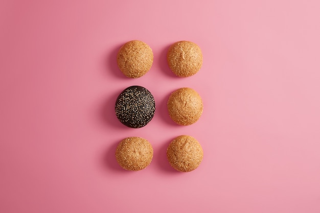 장밋빛 바탕에 두 줄로 배열하는 참 깨와 신선한 햄버거 빵. 패스트 푸드 또는 수제 햄버거 준비하기. 음식 사진. 건강에 해로운 식사 나 다이어트. 둥근 부드러운 브리오 치. 선택적 초점