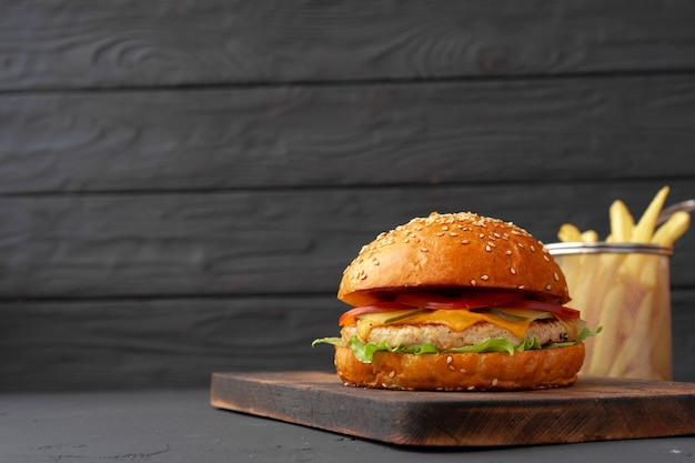 Fresh burger and fries on black wooden background, front view