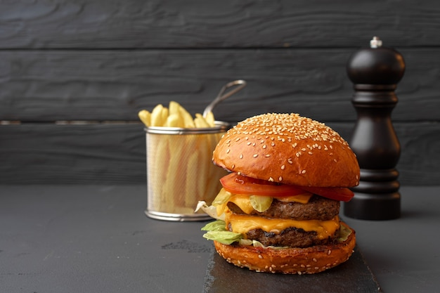 Fresh burger and fries on black wooden background