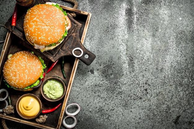Свежие гамбургеры с говядиной и овощами на старом подносе. на деревенском фоне.