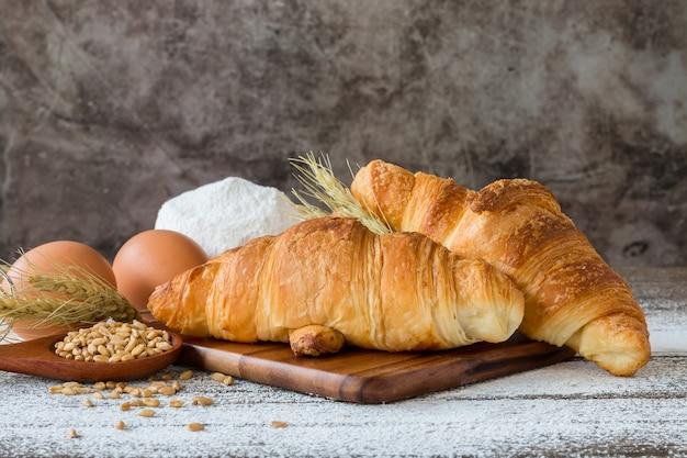 신선한 버터 크루아상, 맛있고 겉은 바삭하고 속은 부드러움 다목적 밀가루가있는 나무 테이블 위에.