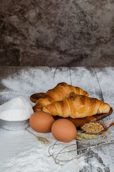 Fresh butter croissant, delicious, crispy outside, soft inside on a wooden table with all purpose flour.