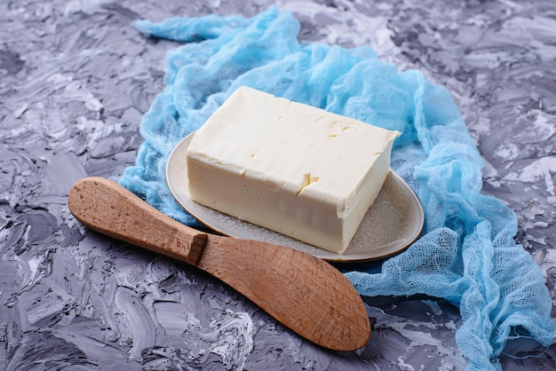 Fresh butter and knife on concrete background