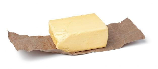 白で隔離されるクラフトペーパーに新鮮なバター