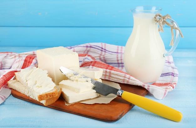 まな板に新鮮なバターとミルクと水差し、色の木製テーブルに