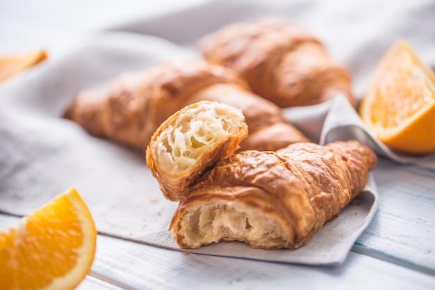 주방 냅킨에 달콤한 오렌지와 신선한 버터 크로와상.