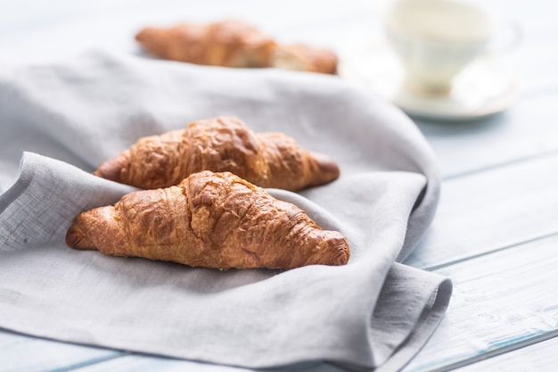 Fresh buttery croissants on kitchen napkin and wooden table.