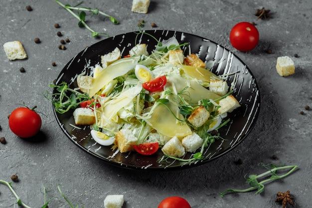 Свежий салат цезарь в черной тарелке на сером столе. вид сверху