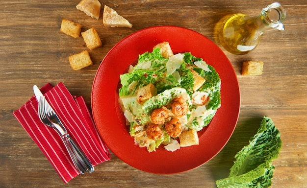 Fresh caesar salad on red plate with parmesan cheese and shrimps on wooden table. top view