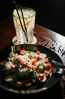 Fresh caesar salad in white plate on dark wooden table. top view copy space.