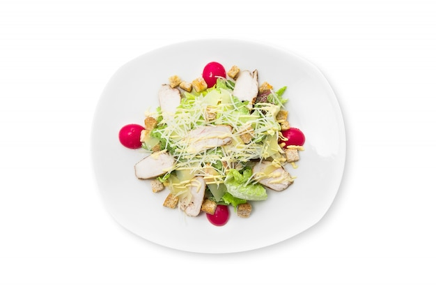 Fresh caesar salad with chicken on a white plate isolated.