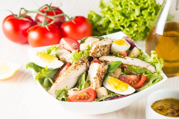 Fresh caesar salad with delicious chicken breast, ruccola, spinach, cabbage, arugula, egg, parmesan and cherry tomato on wooden background. oil, salt and pepper. healthy and diet food concept.