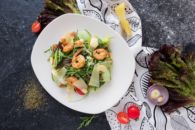 Fresh caesar salad with shrimps on a white plate on dark stone background