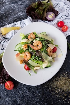 Fresh caesar salad with shrimps on white plate on dark stone.