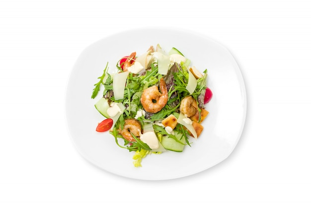 Fresh caesar salad with shrimps on a white plate isolated.