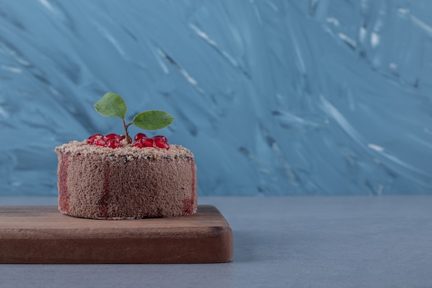 Fresh cake. delicious cake with pomegranate on wooden board