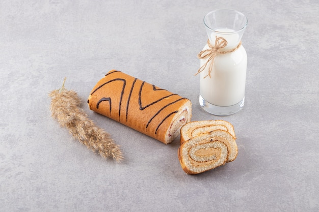 Fresh cake roll with bottle of milk on grey background.