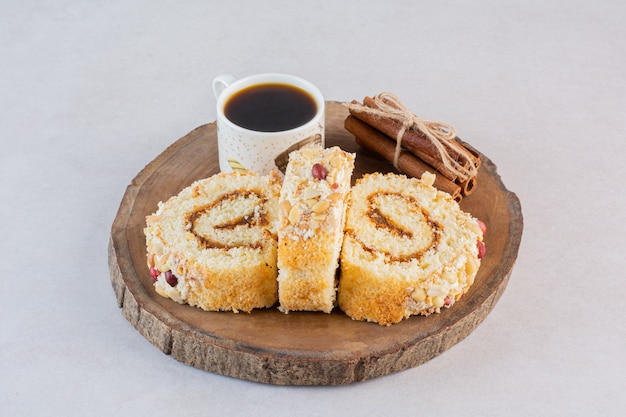 Fresh cake rolls with cup of coffee on wooden board