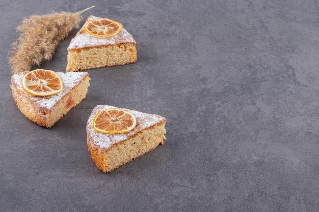 회색 표면에 말린 레몬 조각과 신선한 케이크 조각
