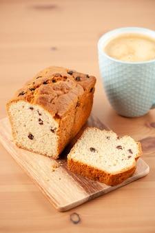 木製のテーブルの上のコーヒーのカップと新鮮なケーキ