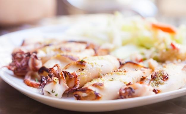 Свежие кальмары подаются в старинном итальянском ресторане (тоскана). дневной свет.