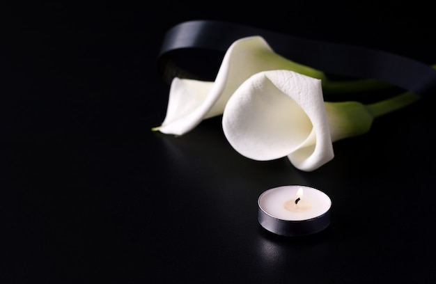 Fresh calla flower next to candles on black