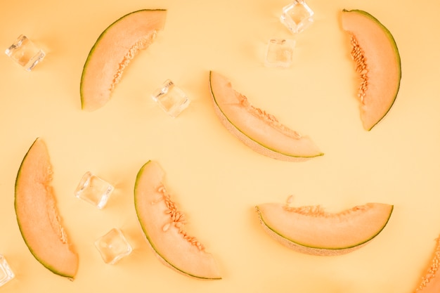 Fresh cantaloupe slices with ice cubes on beige background