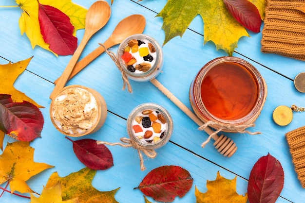 秋のテーブルにヨーグルトと木製カップの新鮮なカプチーノ。