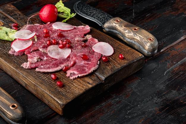 와인 식초 세트가 있는 신선한 카르파초 샐러드, 무와 석류석, 나무 서빙 보드, 오래된 어두운 나무 테이블 배경, 텍스트 복사 공간