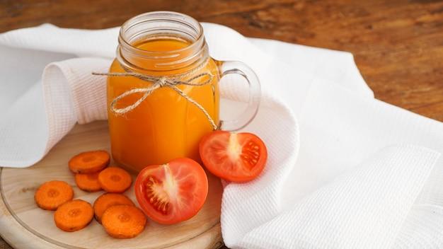유리에 신선한 당근과 토마토 주스와 나무 테이블에 흰 수건. 소박한 스타일. 비타민이 함유된 수제 음료