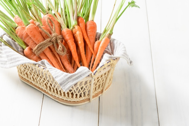 Fresh carrot, baby carrot in basket on white wood background, this vegetable is an exceptionally ric