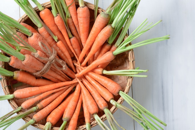 Fresh carrot, baby carrot in basket on white wood background and top view, this vegetable is an exce