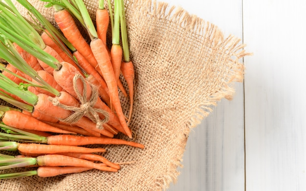 Fresh carrot, baby carrot on sack and white wood background and top view, this vegetable is an excep