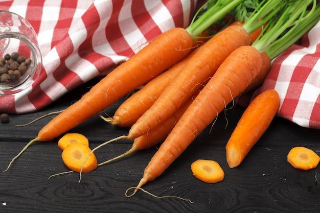 Свежий пучок моркови на темно-черном
