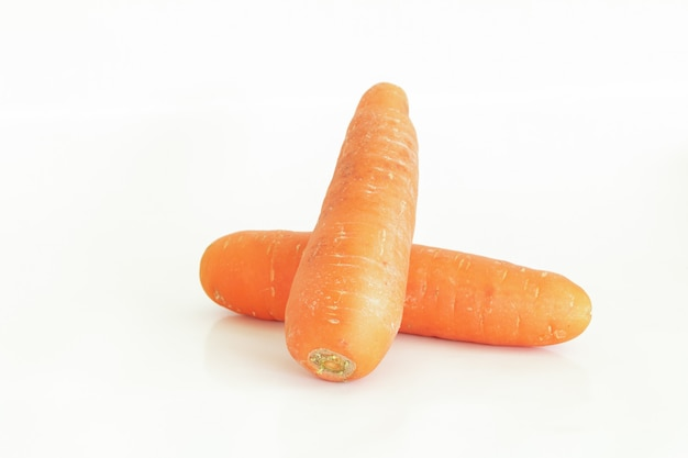 Fresh carrot and cut pieces isolated on white