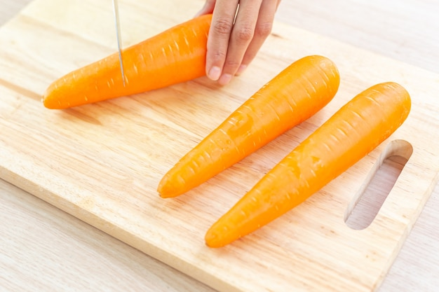 Fresh carrot and cut pieces on wooden cutting board