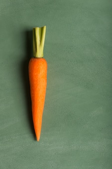 Fresh carrot on the green table