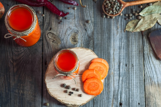 Fresh carrot juice in glass jars, top view