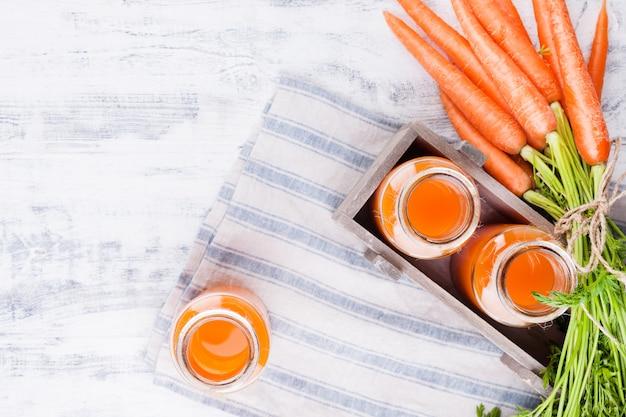 瓶の中の新鮮なにんじんジュース。新鮮なニンジンの葉と飲み物。健康と美容のための春の食べ物