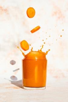 Свежевыжатый морковный сок, брызги из стекла