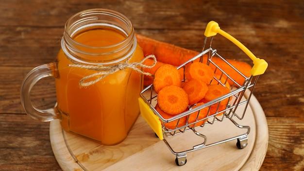 슈퍼마켓 카트와 나무 배경에 신선한 당근 주스. 유리병에 담긴 주스, 수제 음료