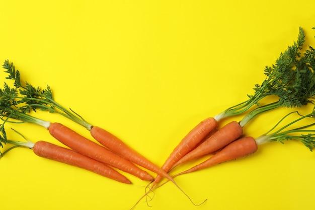 Свежая морковь на желтом фоне, место для текста