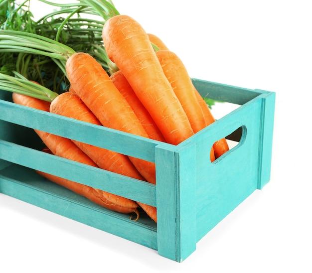 Свежая морковь в деревянном ящике на белом