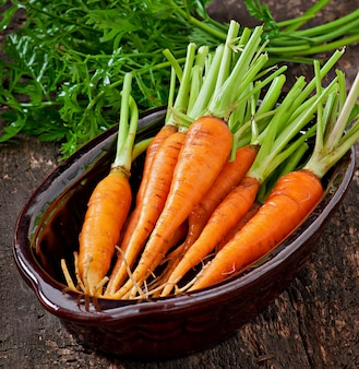 Fresh carrots on old wooden surface