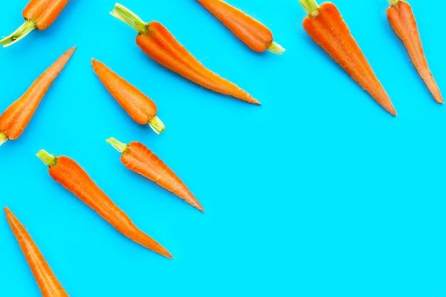 Свежая морковь на синем фоне.